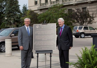 Lord Selkirk and Premier Selinger standing beside the plaque that now hangs on the second floor of the Manitoba Legislative Building.‏